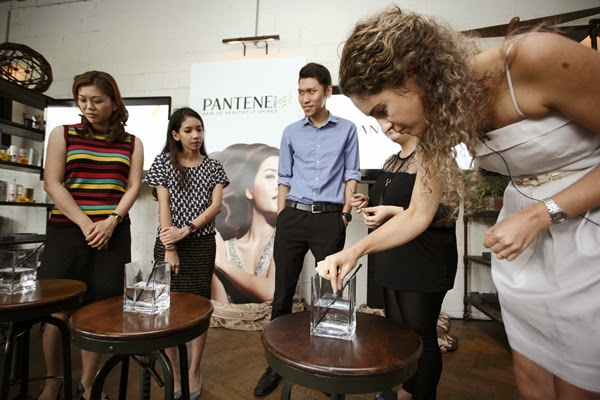 P&G Asia Hair Care Scientist, Lais Koelle analyzing the hair health of three members of the media from the floor.