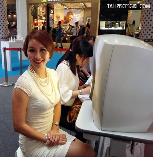 Mrs. Malaysia International 2012, Rachel Sua poses in front of the skin analysis machine